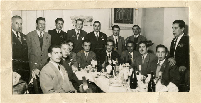 a group of men in suits sit and stand around a long dining table