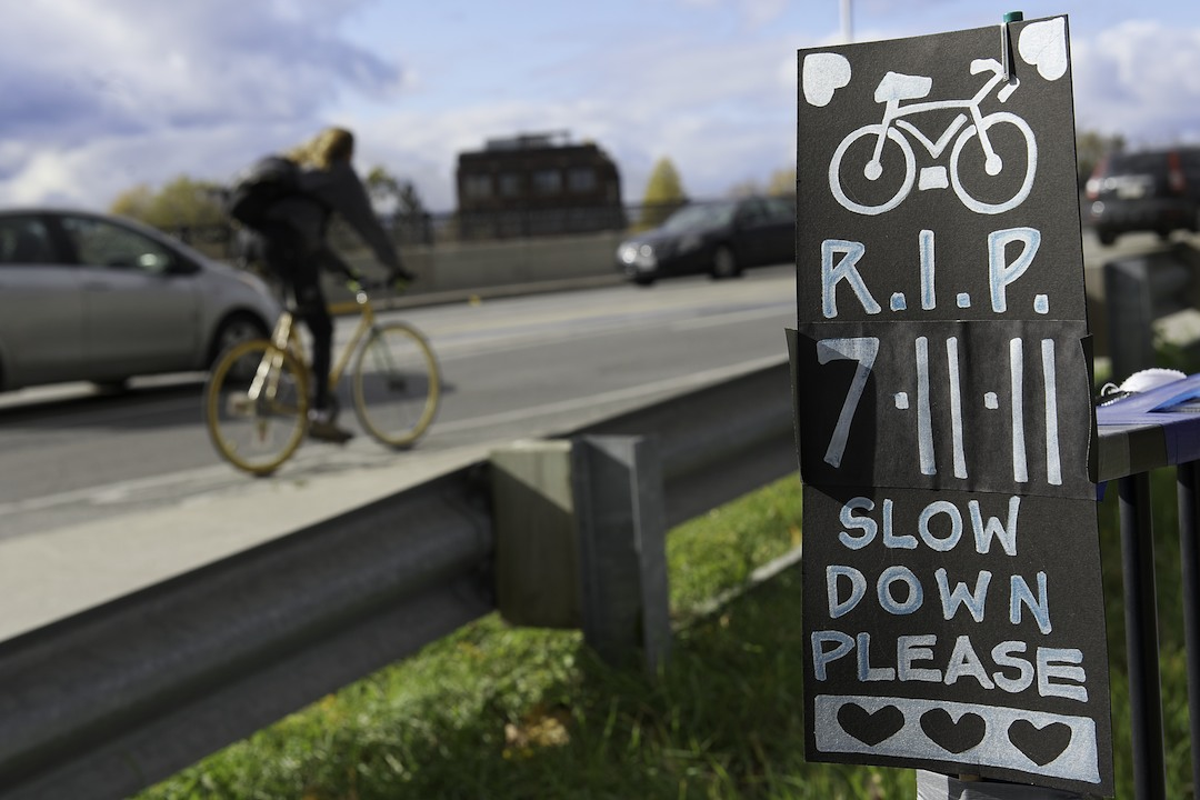 cyclist rides past a memorial poster for Jenna Morrison