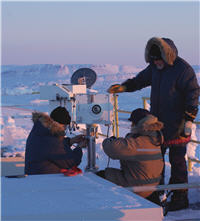 researchers in winter coats install instruments on lab roof