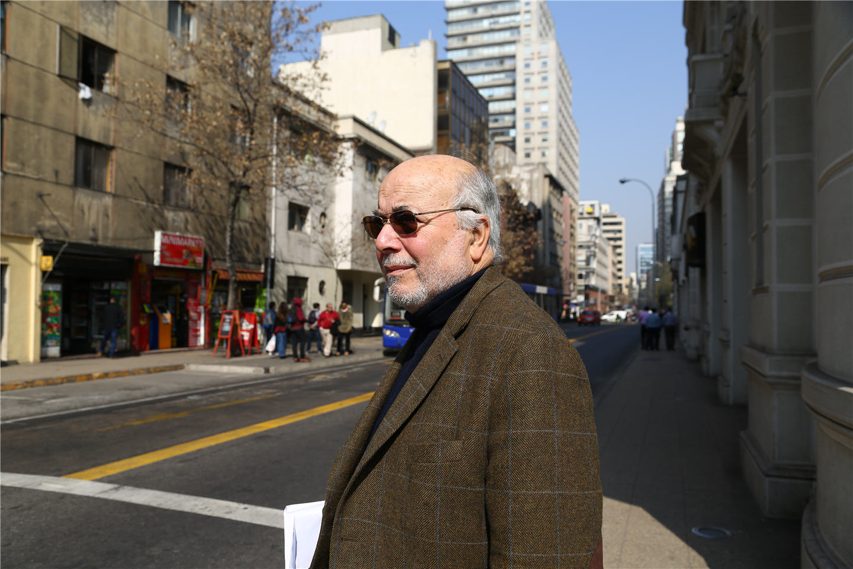 Juan Guzman stands on a street corner wearing sunglasses