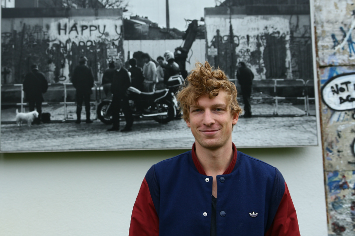 young man stands in front of historial Berlin Wall photo outdoors