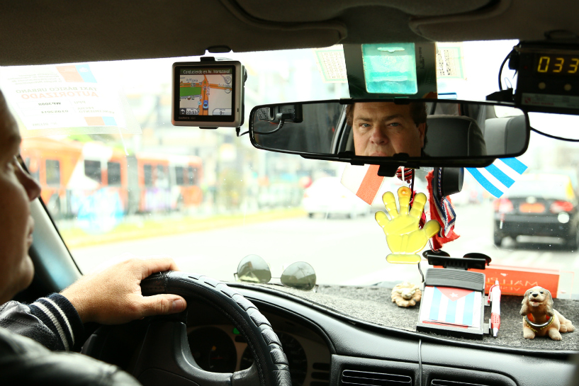 taxi driver looks at camera through rear view mirror