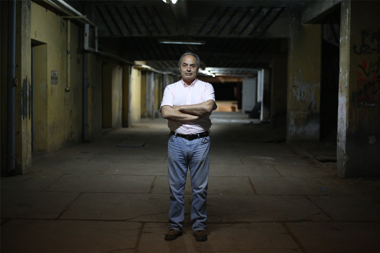 Franco Urbina standing in a dimly lit corridor