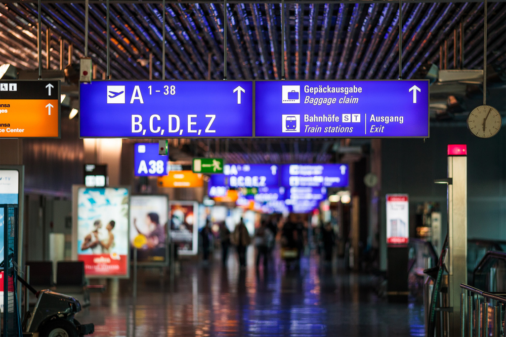 illuminated signs in the Frankfurt Airport terminal, blurred figures in the background