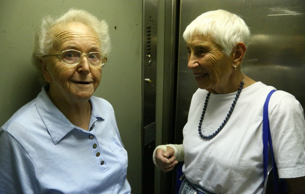 two elderly women in a small elevator