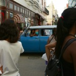 A classic American car from the 50s cuts through a busy pedestrian street
