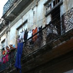 Two women watch the street from a balcony in Old Havana